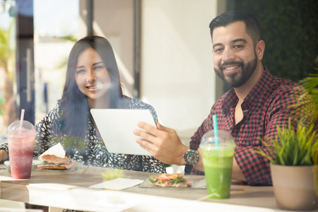 Pretty young Latin couple using a tablet computer at a cafe while eating lunch photo