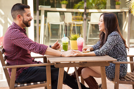 Profile view of a young couple holding hands during a lunch date and having fun photo