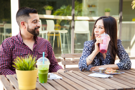outdoor cafe: Young couple of friends having a sandwich and smoothies during a lunch break
