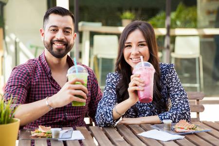 pareja comiendo: Apuesto joven pareja disfrutando de algunos batidos saludables y bocadillos en un caf� Foto de archivo