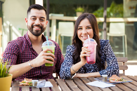 latin couple: Good looking young couple enjoying some healthy smoothies and sandwiches at a cafe