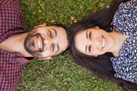 Top view of a good looking young couple relaxing at a park and smiling