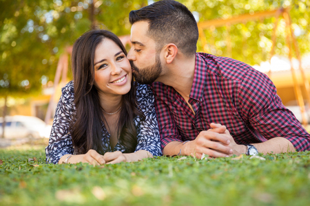 couple nature: Portrait of a gorgeous young Latin brunette relaxing at a park with her boyfriend