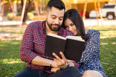 Pretty young couple relaxing at a park and reading a book together