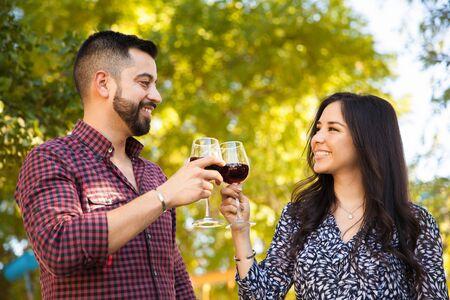 Feliz pareja de jóvenes brindando con vino, mientras que con un picnic al aire libre