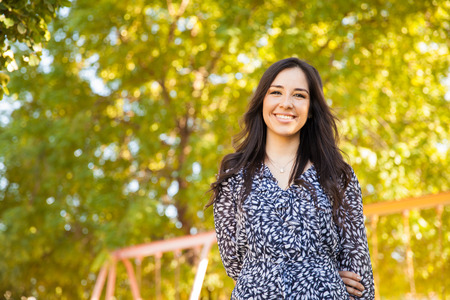 thirties portrait: Portrait of a gorgeous young Hispanic woman hanging out at a park and smiling