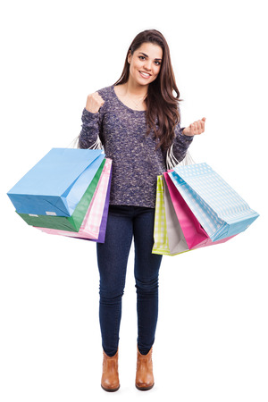 carrying: Full length portrait of a cute young woman carrying shopping bags on both her arms and smiling