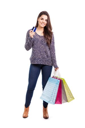woman buying: Full length portrait of a pretty young woman carrying a few shopping bags and holding a credit card