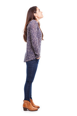 Full length profile view of a young brunette in casual clothing looking up towards copy space Stock fotó