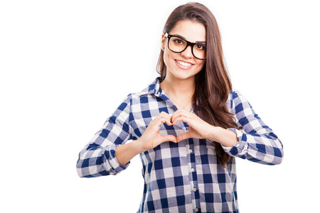 glass heart: Good-looking young Hispanic woman making a heart sign with her hands and smiling Stock Photo