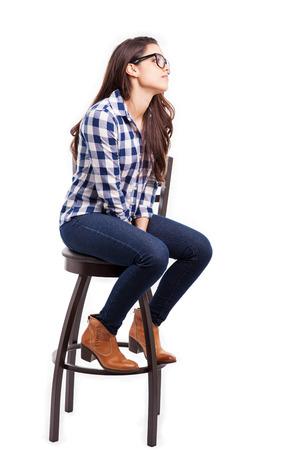 椅子に座っているとコピーの領域に向かっているかわいい流行に敏感な女の子のプロフィール