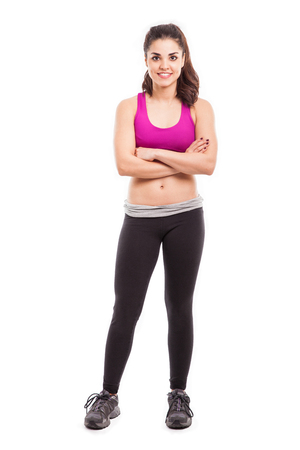 Portrait of a cute young female athlete with her arms crossed in a white background photo