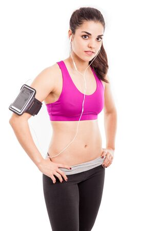 earbuds: Portrait of a beautiful and strong female athlete with earbuds and an armband ready to go for a run Stock Photo