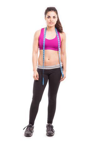 mujer deportista: Retrato de cuerpo entero de una hermosa mujer joven en traje deportivo con una cinta métrica alrededor de su cuello Foto de archivo