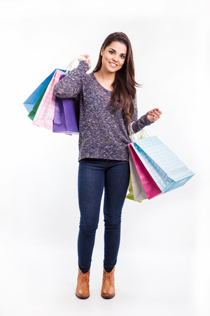 Beautiful young Hispanic woman carrying a few shopping bags and smiling Stock Photo