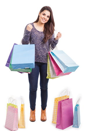 Beautiful Hispanic young woman surrounded by many shopping bags and smiling photo