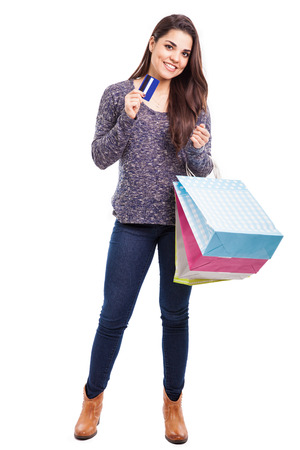 Studio portrait of a cute Latin brunette carrying some shopping bags and using a credit card photo