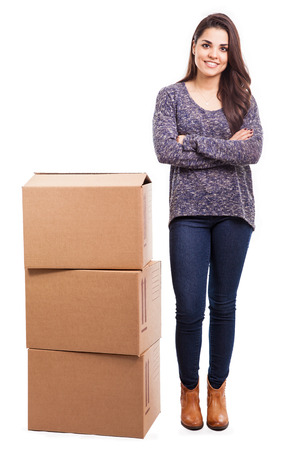shipped: Pretty young Hispanic woman standing next to some parcels ready to be shipped
