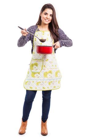 앞치마를 입고 점심을 요리하는 잘 생긴 젊은 주부의 전체 길이 초상화