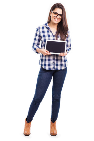 white isolated: Full length portrait of a hipster girl showing a tablet computer screen in a white background Stock Photo