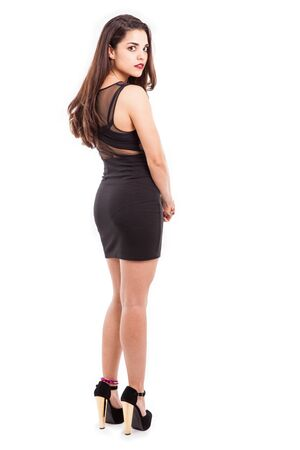 Beautiful young Latin brunette looking all sexy on a black dress and high heels 版權商用圖片