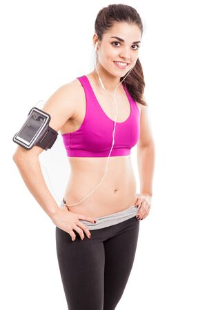 earbuds: Happy athletic girl wearing an armband and earbuds and listening to some music from her smartphone