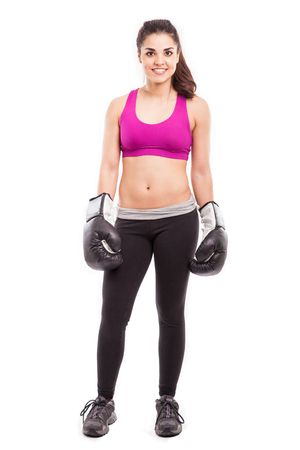 Portrait of a cute Hispanic young woman wearing boxing gloves and ready for training Stock Photo