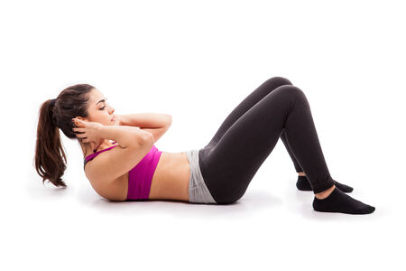 crunches: Profile view of a pretty girl in sporty outfit doing some crunches on the floor in a white background