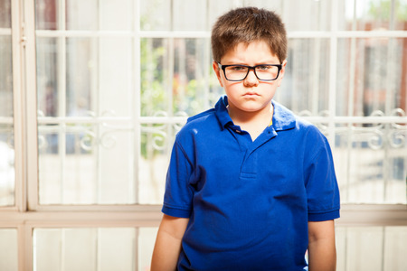 Little blond kid with glasses looking all angry and pissed off at home