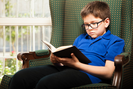 tween: Nerdy young kid with glasses reading his favorite book while relaxing at home Stock Photo