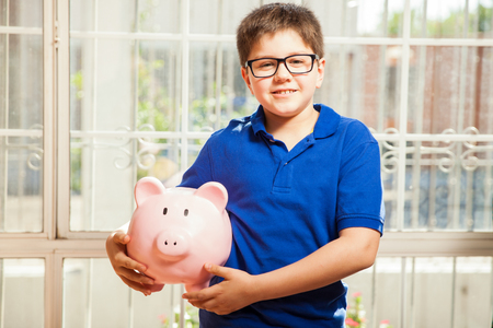 piggy bank: Portrait of a cute nerdy boy carrying a piggy bank with his savings and smiling