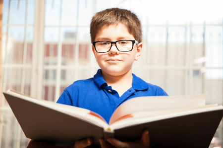 mixed raced: Portrait of a cute kid with glasses reading a big book at home Stock Photo