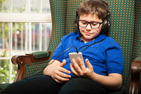 mixed raced: Mixed raced tween wearing glasses and heaphones listening to music from a smartphone at home Stock Photo
