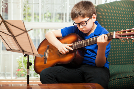 chords: Little white kid with glasses practicing some new guitar chords at home
