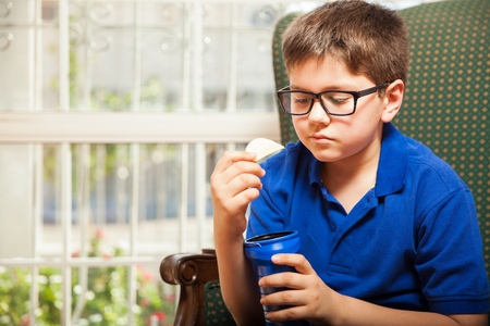 junk: Portrait of a blond kid with glasses eating some unhealthy chips at home