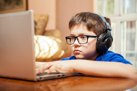 kids playing video games: Tween gamer wearing glasses and headphones playing a videogame on a laptop Stock Photo