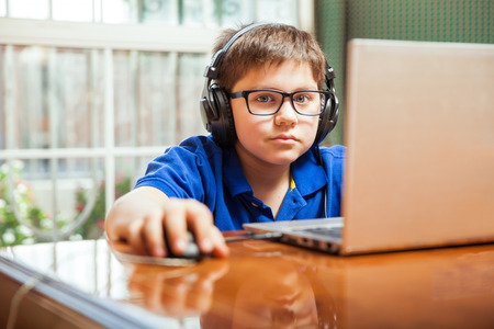 Little gamer with headphones playing video games on a laptop computer