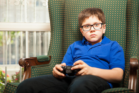 home video: Little boy with glasses relaxing and playing video games at home