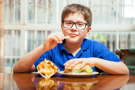 latin food: Young boy with glasses eating french fries and a burger at home Stock Photo