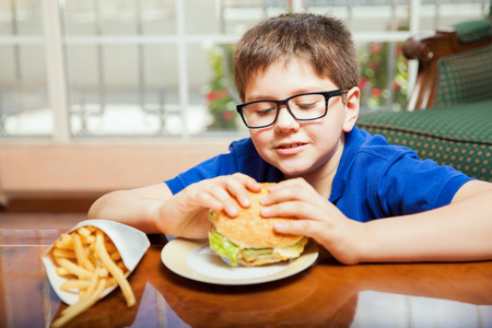 mixed raced: Little blond boy with glasses eating junk food at home