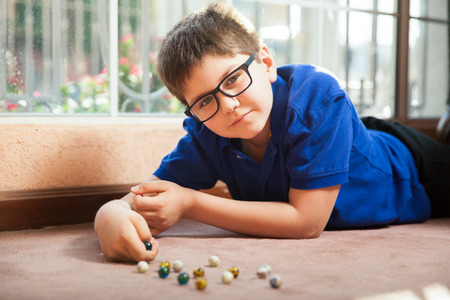 mixed raced: Portrait of a little boy with glasses lying on the carpet floor and playing with some marbles at home Stock Photo