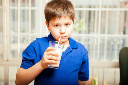 eye contact: Blond kid drinking his milk with a straw at home and making eye contact