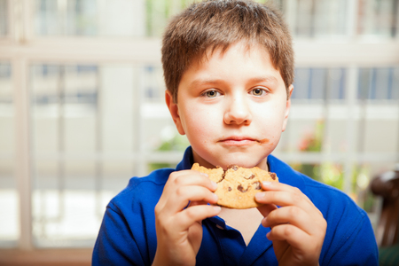 smeared: Portrait of a little blond boy enjoying a chocolate chip cookie at home