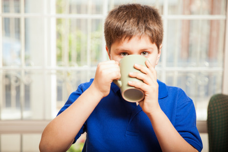 eye contact: Young boy drinking some coffee from a mug and making eye contact