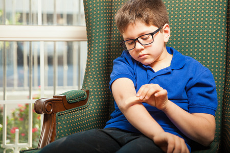 adhesive bandage: Blond kid putting on an adhesive bandage on a cut on his arm