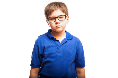 blank expression: Studio portrait of a young boy with glasses and a blank expression