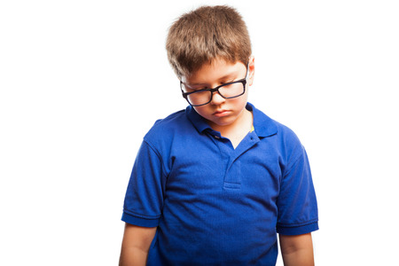 Studio portrait of a little boy with glasses looking all sad and lonely photo