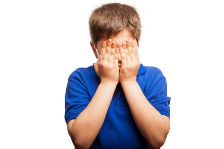 niño llorando: Pequeño muchacho rubio que cubría su rostro con ambas manos sobre un fondo blanco