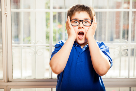 teen boy face: Portrait of a cute young boy with glasses looking shocked and surprised about something Stock Photo