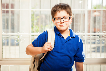 mixed raced: Portrait of a cute young boy with glasses carrying a backpack and standing ready for school Stock Photo